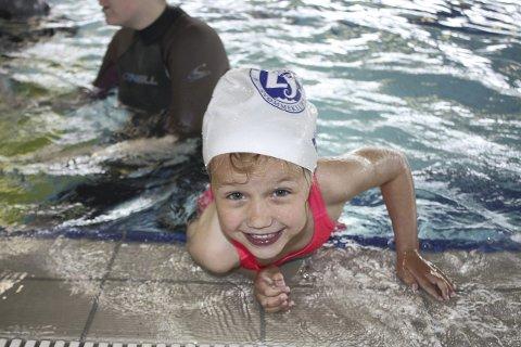 I LEK: Frøy Helland Kalstad har akkurat hoppet fra kanten ut i bassenget, og er på vei opp for å gjøre det igjen.