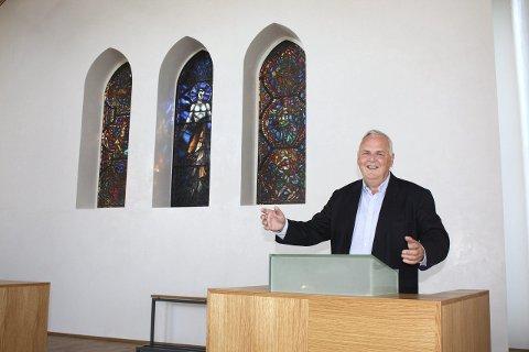 PÅ TALERSTOLEN: Talerstolen er ny, blyglassmaleriene de samme og sokneprest Espen Feilberg Jacobsen utstråler mye glede over igjen å ha gudstjenestene i Nordstrand kirke. Foto: Aina Moberg