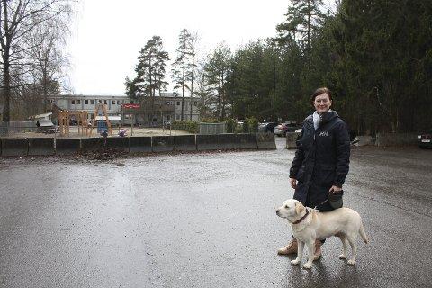 BETONGKLOSSER: Kari Leirås Nilsen og hunden Ronja på parkeringsplassen ved Frierveien barnehage bak Ekeberghallen. Nilsen ønsker at klossene flyttes oppover på plassen slik at bilister som kommer sørfra kan kjøre inn og parkere her for å slippe unna bommen i Ekebergveien. FOTO: Aina Moberg