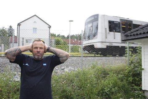 Vil ha STØYSKJERM: Håvard Svang bor ved Godlia stasjon med skinnegangen få meter fra husveggen.                                                           Dersom Sporveien ikke sørger for støyskjerm forbi huset, vurderer han å finansiere den selv.  FOTO: AINA MOBERG