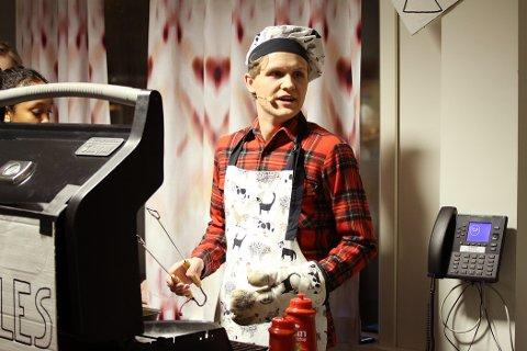 PØLSEPAUSE: Kristian Willassen tok med seg rollen som grillentusiast-far inn i pausen og serverte tilskuerne pølser i kafeen.