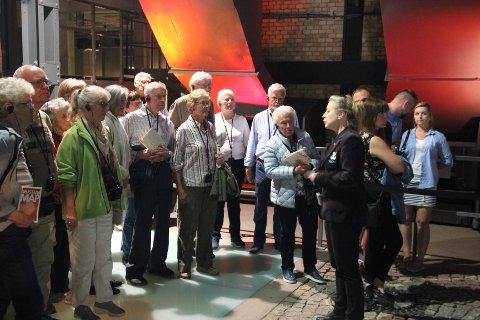 En alvorspreget gruppe på besøk i Museet til minne om Warszawaoppstanden i 1944