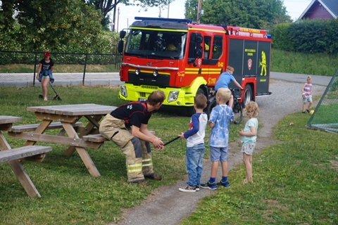 Brannvesenet kom for å inspisere og godkjenne bålet. De tok seg god tid til å slå av en prat med barna
