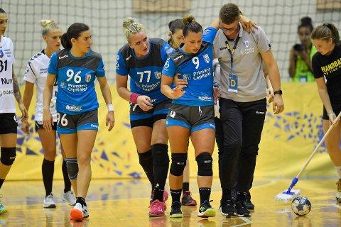 SKADET: Nora Mørk hjelpes av  banen etter at hun fikk en smell i kneet i sin debut for Bucuresti søndag. Foto: Alex Nicodim/NTB scanpix