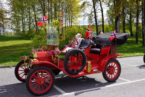 """RØDT, HVITT og BLÅTT: """"Se, en hvitstammet bjerk oppi heien,  rammer stripen med blåklokker inn  mot den rødmalte stuen ved veien. Det er flagget som vaier i vind"""". Ikke blåklokker eller rødmalt stue, men en rødmalt Ford fra 1910 pyntet med både bjørkekvister og flagg."""