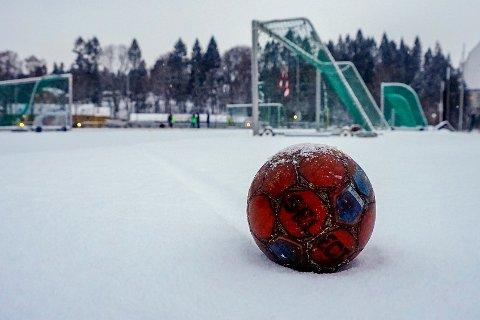 En forlatt fotball på snødekket Ferd Stadion i Oslo mandag ettermiddag, etter at hovedstaden i løpet av dagen fikk et lite påfyll av hvit nedbør.