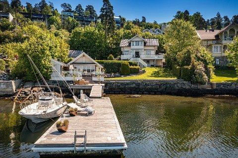 Eiendommen selges inn med badehus og privat bryggeanlegg. Ulovlige strandtiltak, mener Plan- og bygningsetaten.