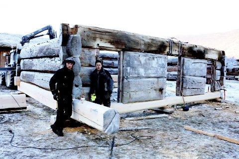 Enorme dimensjonar: Geir Sletten (t.v.) og Svein Bakken laftar opp att den gamle stallen frå Kvam. Stokken over dørene veg godt over eitt tonn.
