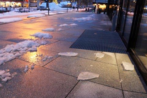 RAMLET NED: Isklumpene og snøensosm fredag formiddag falt ned på den steinlagte plassen foran Kystens Hus.