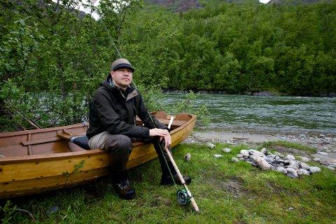 Ronny Løvoll har dratt båten på land, i sikkerhet for de frådende vannmassene i den flomstore elva. - Jeg har ikke sett en fisk så langt.