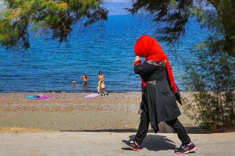 KONTRAST: En kvinnelig flyktning beskytter seg mot heten på Lesbos, mens turistene på stranda i Petra nyter varmen.