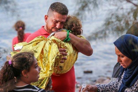 VELKOMMEN TIL EUROPA: En Syrisk far knuger sin lille datter på stranda i Eftalou helt nord på øya Lesbos.