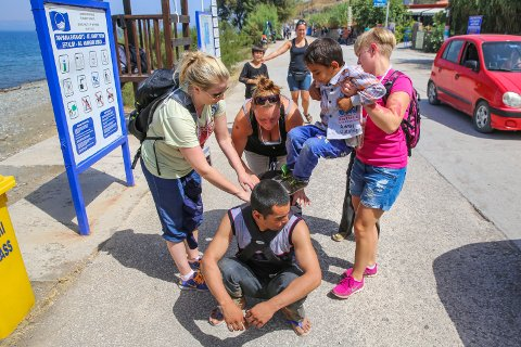 HJELP: Småbarnsfaren hadde aldri brukt en bæresele før han kom til Lesbos. Her hjelper Mona Kjeldsdatter Martinsen (33, til venstre), Marthe Langstrand (33) og Monica Nyborg (32) til for å få gutten på plass.