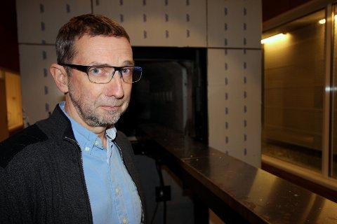 SJEF FOR KREMASJONER: Pål Thomas Berg (54) er krematoriesjefen i Tromsø. I bakgrunnen ser vi den sentrale enheten i kremasjonsprosessen; forbrenningsovnen. Foto: Bengt Nielsen