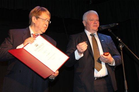 BEVIS: Tore Skoglund viser fram det skriftlige beviset på tildelinga.