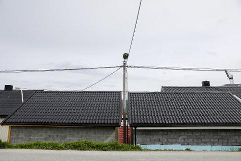 TETT: Slik står lavspentmasta, mellom to garasjer i Lars Hagerupsveg. Troms kraft reagerer, og mener nybyggene er i strid med forskriften om Elektrisk Forsyningsanlegg.