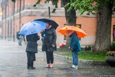 Menneskene på bildet har paraplyer, ikke ulik den festlige paraplyemojien til MET på deres rekordmelding på Twitter. Og mer regn skal det bli!