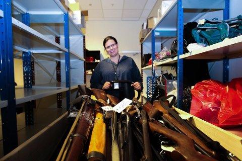 KAN INNDRAS: Seksjonsleder Stina Bakke Eriksen med noen av våpnene som ble innlevert i forbindelse med våpenamnestiet i 2017. Nå vil politiet inndra våpenkortene til pistoleiere som ikke fyller kravene til å eie handvåpen. Foto: Linn Bertheussen