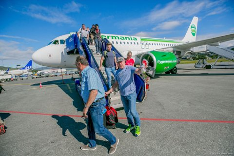 Glade fisketurister stiger av flyet i Tromsø.