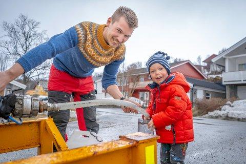 OVER VEIEN ETTER VANN: Pappa Andreas Olsen (29) og tre år gamle Oscar må hente vann i vanntanker, etter at vannet forsvant natt til søndag. Nå har kommunen sagt at gravingen først skjer på torsdag.