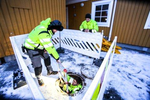 FROSNE RØR: Kjartan Nygård hjelper Svein Kåsereff opp fra vannkummen utenfor Norlandia-bygget på Storslett. Vannledningen inn til bygget var bunnfrosset. I bakgrunnen Lasse Bjørn.