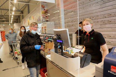 FØRST I KØA: Gunnar Larsen hadde tatt turen fra Tromsø. Her sammen med butikkmedarbeider Camilla Jernberg i kassa.