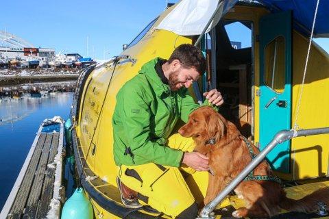 TROFAST FØLGESVENN: Guylee Simmonds (29) og hans faste reisepartner på bakdekket av båten hans, «Stødig» som ligger på Skattøra Marina.  Retrieveren «Shackleton» er oppkalt etter den britiske polfareren Ernest Shackleton, kjent for å ha reddet hele mannskapet sitt under en ekspedisjon.  - Vi likte tanken på å ha en Shackleton med oss på tur. Han har tilpasset seg livet på havet veldig bra, forklarer