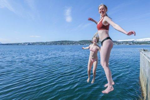 IDYLL: Celine Remmer og Synne Rognmo fant seg en fredelig plass i sola på piren til Tomasjordnes. Her hopper de ut i havet for både dagens og årets andre bad.
