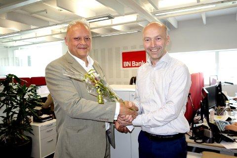 Forbrukerrådets fagdirektør Jorge Jensen overrekker blomster til BN Bank-direktør Gunnar Hovland.