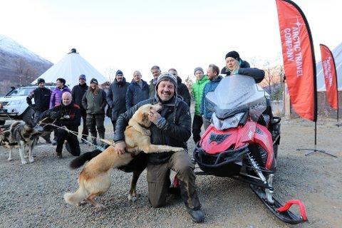 STORFAMILIEN: Tom Frode Johansen i Lyngsfjord Adventure får en velfortjent kos av hunden. I bakgrunnen representanter fra flere av bedriftene som nå er gått inn i nystartede Arctic Travel Company og deres bookingpartnere: Arctic Explorer, Kirkenes Snøhotell,  Lyngsfjord Adventure og Tromso Travel.