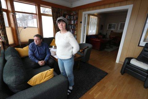 UTSIKT MOT GRAVEMASKIN: Bente Kristin Haugan og Georg Jensen hjemme i stua som har utsikt mot en gravemaskin som står uvirksom i snømassene nedenfor.