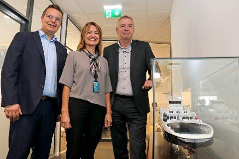 GRØNNE PENGER: Finansdirektør Trygve Tofte i Torghatten, Tone Soleng Wilsgaard i DNB og adm.dir Torkild Torkildsen i Torghatten foran ett av nybyggene selskapet nå har fått 1,1 milliarderi såkalt grønt lån for å finansiere.