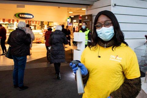 VAKTER VED HVER DØR: Vekterne på City Syd og andre kjøpesentre delte ut munnbind til kundene. Effie Kumi bistod med antibac.