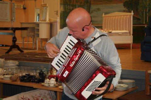 MUSIKALSK INNSPILL: Auksjonarius i orgelkomiteen og Gjøvik-ordfører, Torvild Sveen, viste at han har flere talent å spille på, og dro på med noen toner på et av trekkspillene som skulle auksjoneres bort i herredshuset lørdag.