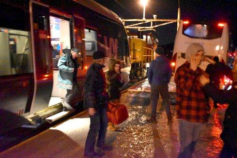 Beklager: Bane Nor beklager at det tok så lang tid å få hentet ut passasjerene fra toget som kjørte på et vindfall nord for Bleiken fredag kveld. Her er passasjerene på veg over i ventende busser, på Bleiken stasjon.
