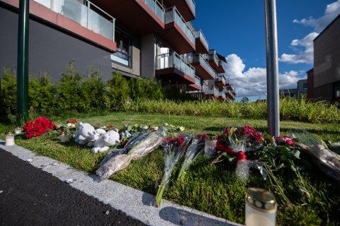 PREGET NABOLAG: Det er lagt ned blomster, lys og bamser utenfor blokka i Lørenskog hvor to små barn ble funnet drept på søndag.