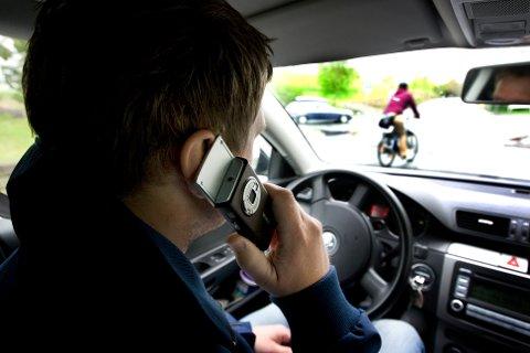 TRONDHEIM  20090513: Mann prater i mobiltelefon mens han kjører bil. Mobilbruk i bil. Ulovlig. Bryter loven. Trafikkfarlig.  Foto: Gorm Kallestad / SCANPIX  NB! Modellklarert