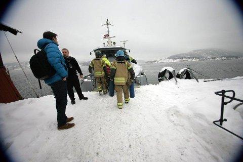 Tok båten: Brannmenn i ferd med å gå om bord i Oscarsborgbåten for å komme seg over og slokke brann