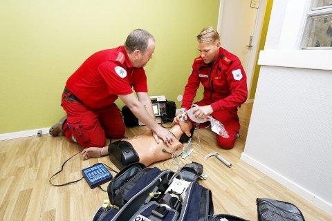 Realistisk: Slik ser det ofte ut når ambulansepersonell gir livreddende hjelp til folk hjemme. Henning Østenheden (til venstre) og Espen Holbræk Hivand i aksjon.