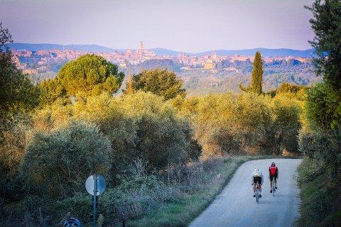 (Bilde 1) VAKKERT: Mange av etappene i sykkelrittet har spektakulær utsikt. Her med middelalderbyen Siena i bakgrunnen.  FOTO: Guido P. Rubino/L'Eroica /
