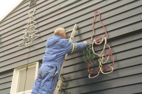I STIGEN: Tore Karlsen må opp i stigen flere ganger mens han pynter til jul. Det tar rundt en uke å pynte hele huset.