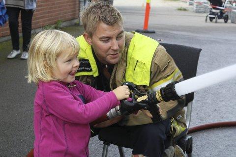 KONSENTRERT: Mari (3 1/2) får veiledning av underbrannmester Michael Christensen om hvordan hun skal slukke en brann med stor brannslange. Trærne bak brannstasjonen ble vannet godt denne lørdagen.