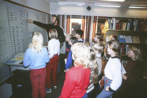 PÅ BESØK: Skoleklasse på besøk på elverket, Harald Tinjar forteller om fjernstyring av strømmen i Ski. Foto 1986 Harald Stokkeland