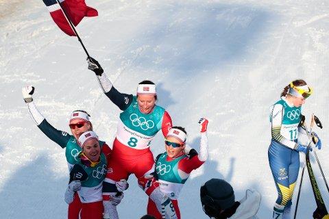 Marit Bjørgen løftes på gullstol av de øvrige norske jentene, Heidi Weng, Ingvild Flugstad Østberg og Ragnhild Haga.