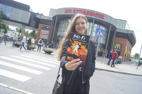 """SKI-FI: Jenny Jordahl fra Ski er forfatteren og illustratøren bak tegneserien """"Ski-Fi Solnedgangen som forsvant"""". Her foran Ski storsenter, som også er en svært sentral del av tegneserien."""