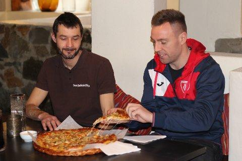 FAVORITT: Follo Hks spillende trener Martin Lysdal Hansen har allerede trykket Don Pablos Pizza til sitt bryst. Det er selvsagt daglig leder Pablo Lopez (t.v.) fornøyd med. Undertegnede var fornøyd med å kunne hjelpe Follo-spilleren med å spise opp Follo pizza'n.