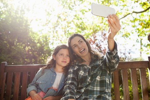 Happy mother taking selfie with daughter while sitting on wooden bench at backyard