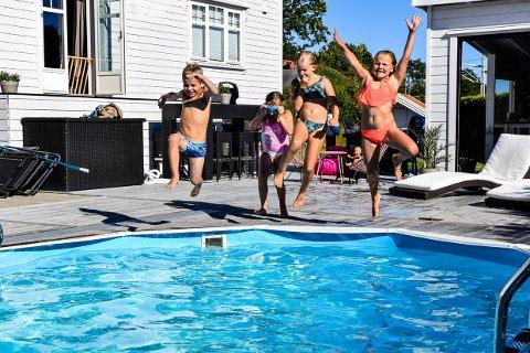 BADEGLEDE: Emma og Filip Eggar Foldvik, Cornelia Andersen og Amelia Strøm koser seg med basseng i hagen. De tenker ikke på at det kan bli vondt i ørene etterpå.