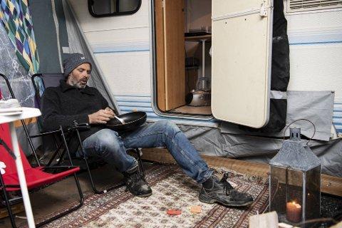 Krister Johnsen har alt han trenger i campingvognen og holder varmen med tjukke klær, stearinlys og sentralvarme.