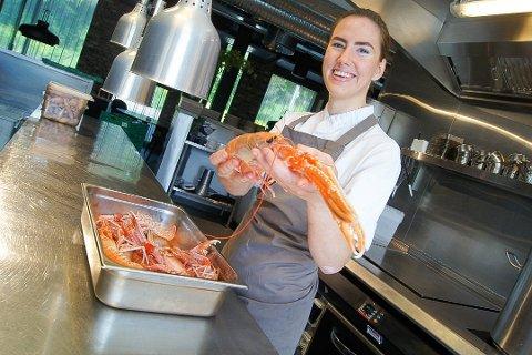 """NY RUNDE: 22 år gamle Celine Ekholt har kvalifisert seg for en ny runde i """"Årets unge kokk"""" og skal konkurrere mot tre andre unge kokker under 25 år. På bildet tar hun godt tak i sjøkrepsen ved en tidligere anledning."""